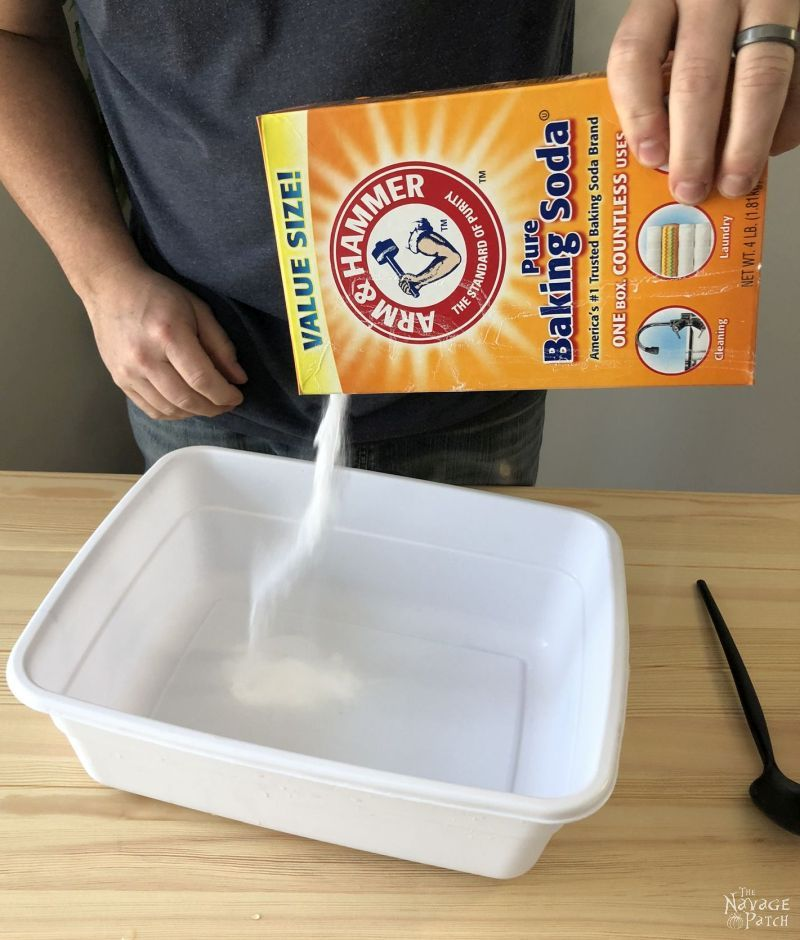 man pouring baking soda into a plastic tub