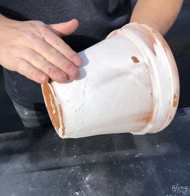 man rubbing excess baking soda from a faux aged terra cotta pot