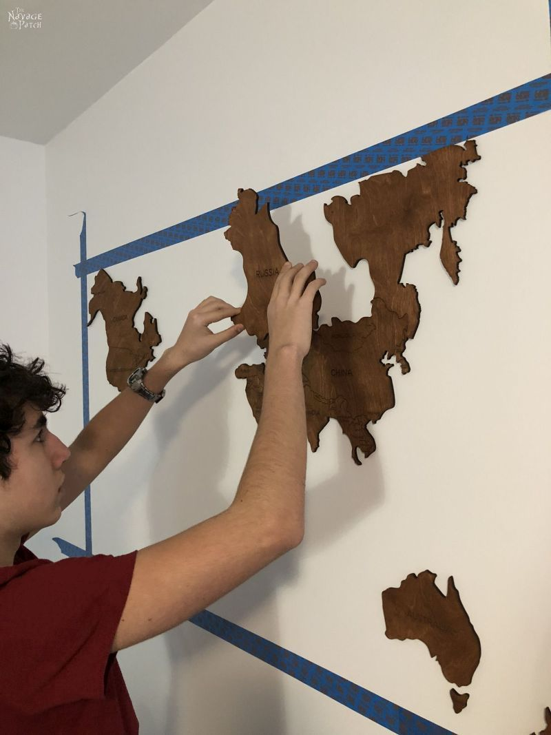 boy sticking wooden country on a wall