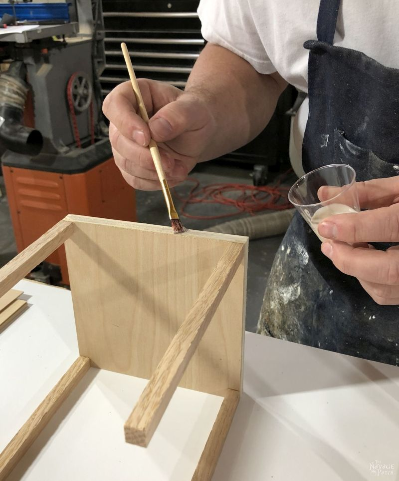 brushing glue on a wooden frame