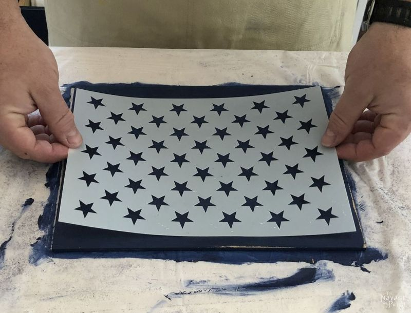 positioning a flag star stencil on a painted piece of wood