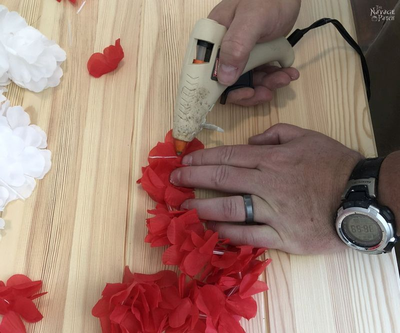 applying hot glue to the end of the lei