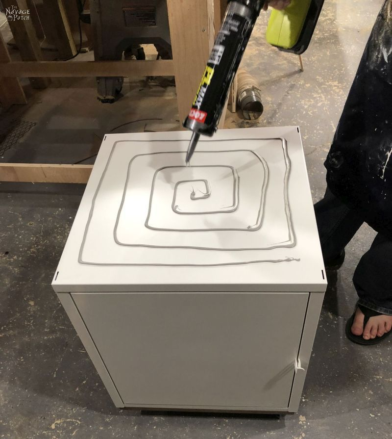 applying adhesive to a metal cabinet