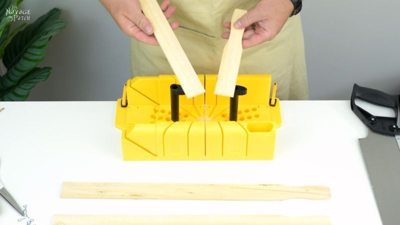 cutting a piece of wood for a magnetic poster hanger on a miter box