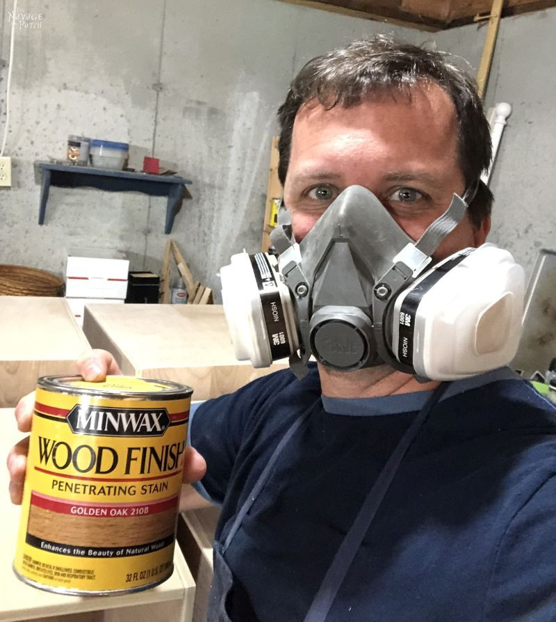man holding a can of stain and wearing a respirator