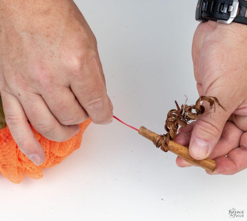 putting the stem on a shower pouf pumpkin