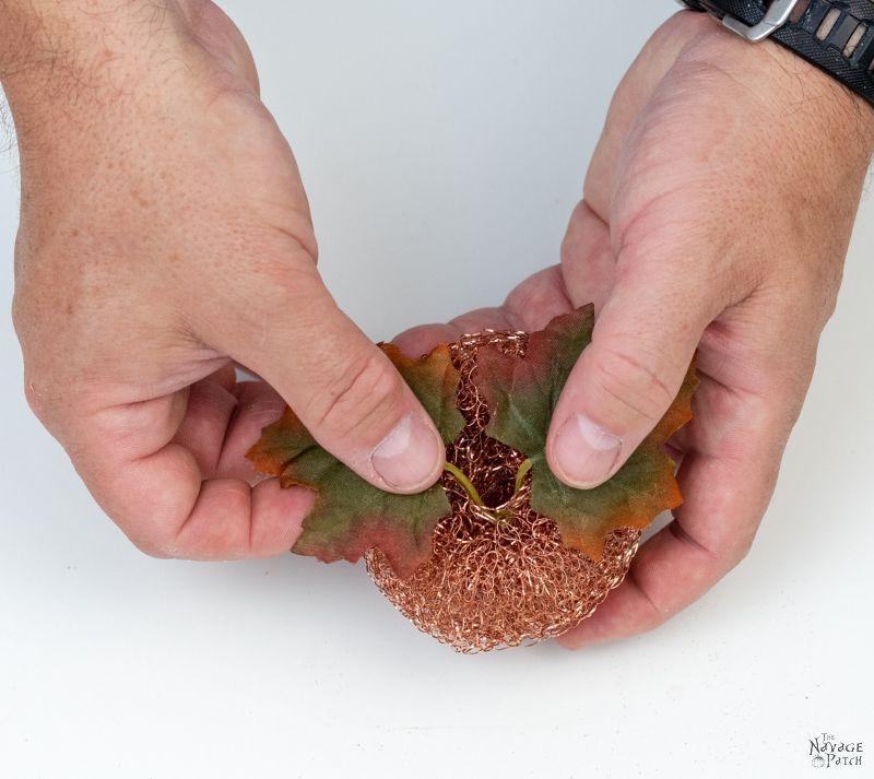 adding fake greenery to make a copper mesh pumpkin