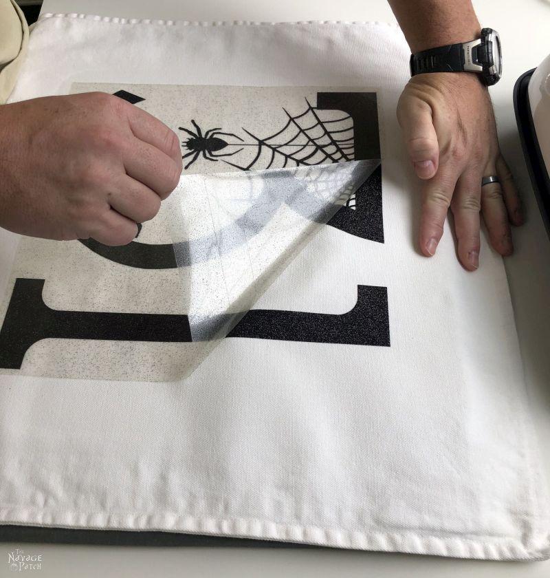 peeling the carrier sheet from a diy halloween pillow
