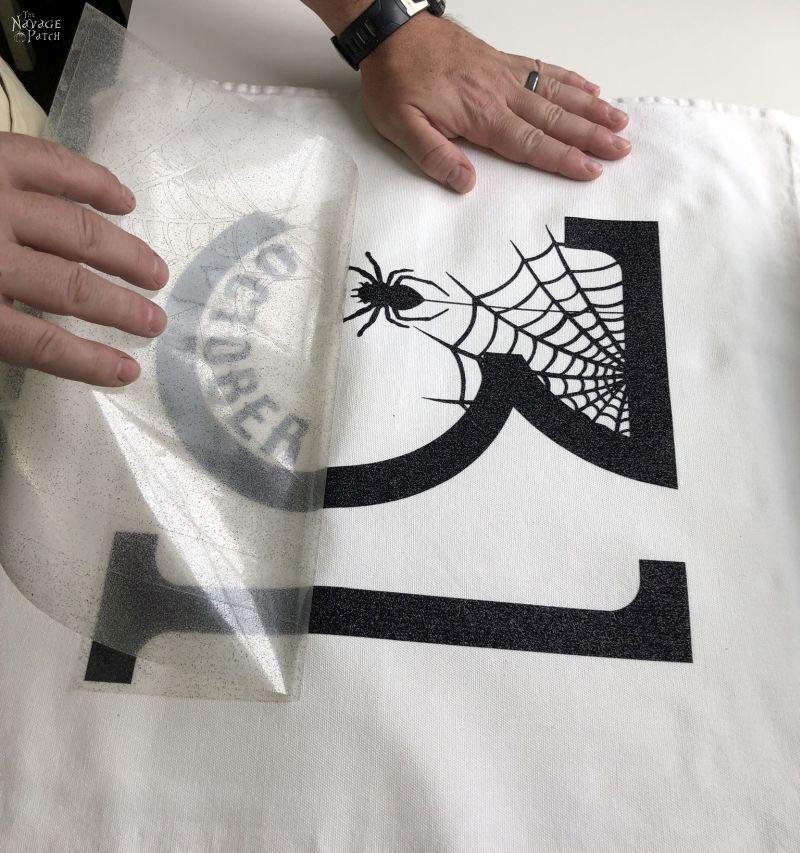 peeling the transfer sheet from a diy halloween pillow