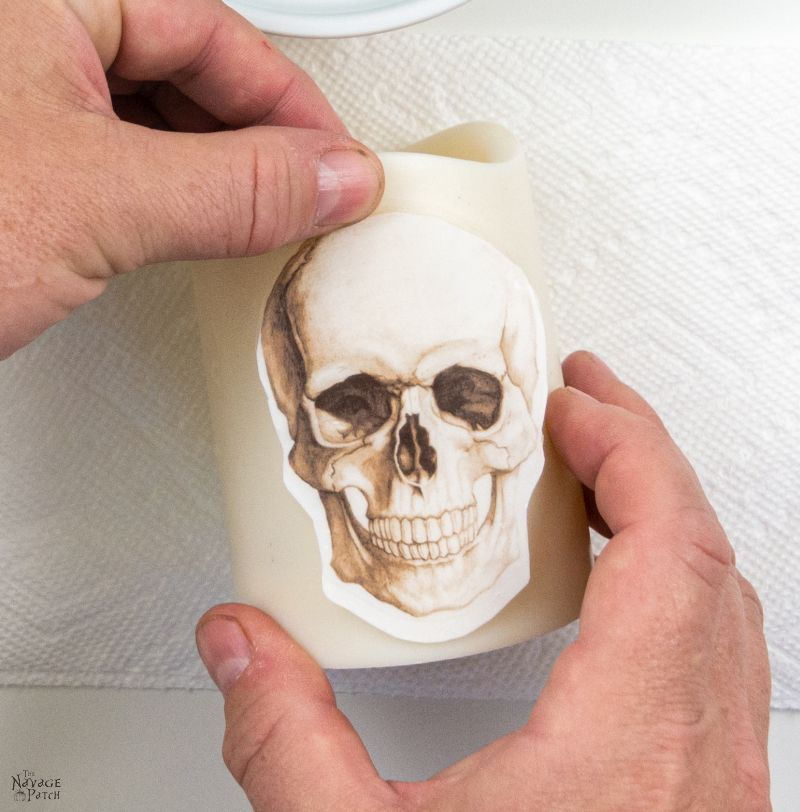 applying a waterslide decal to a DIY halloween candle