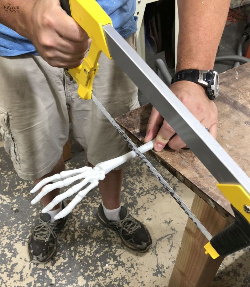 cutting a plastic skeleton arm with a hacksaw