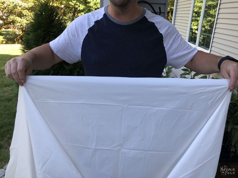 man holds white table cover