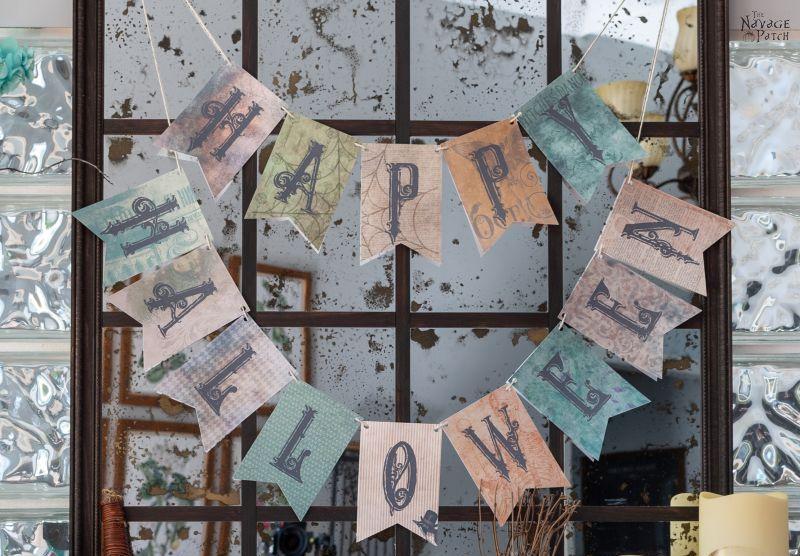 happy halloween garland hanging across an antique mirror