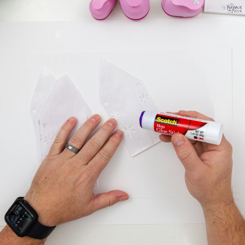 applying glue to paper bags to make snowflake stars
