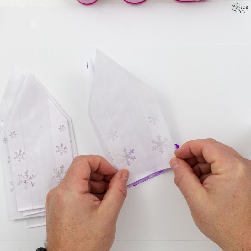 stacking cut paper bags to make 3-d snowflake stars