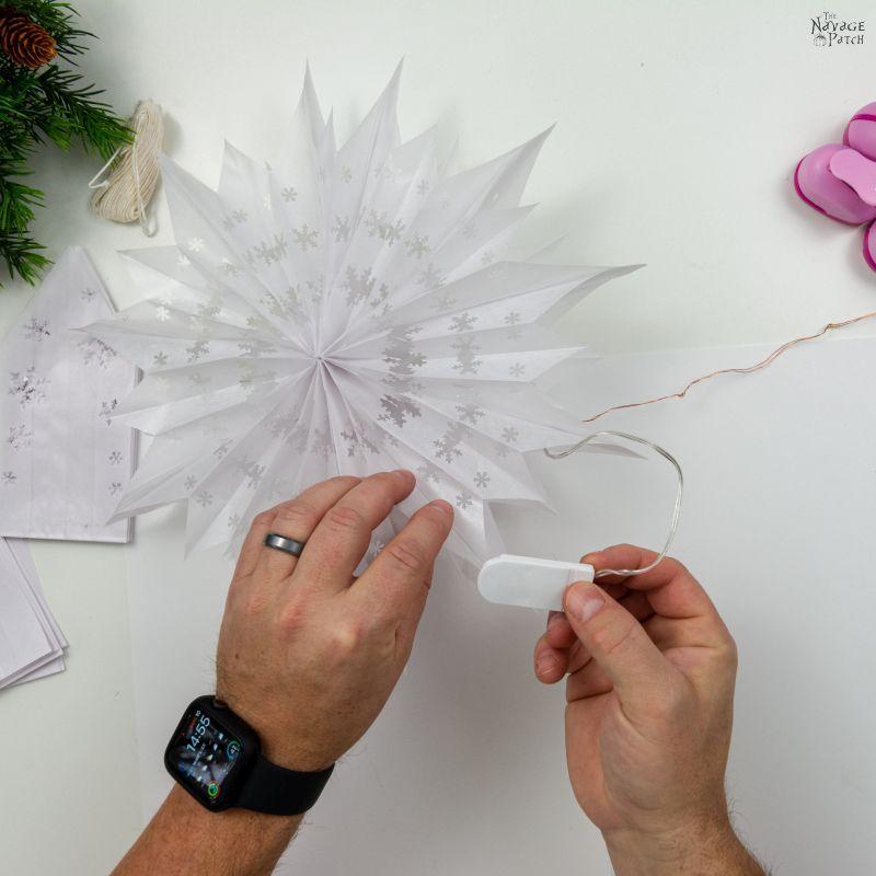 weaving fairy lights through a snowflake star
