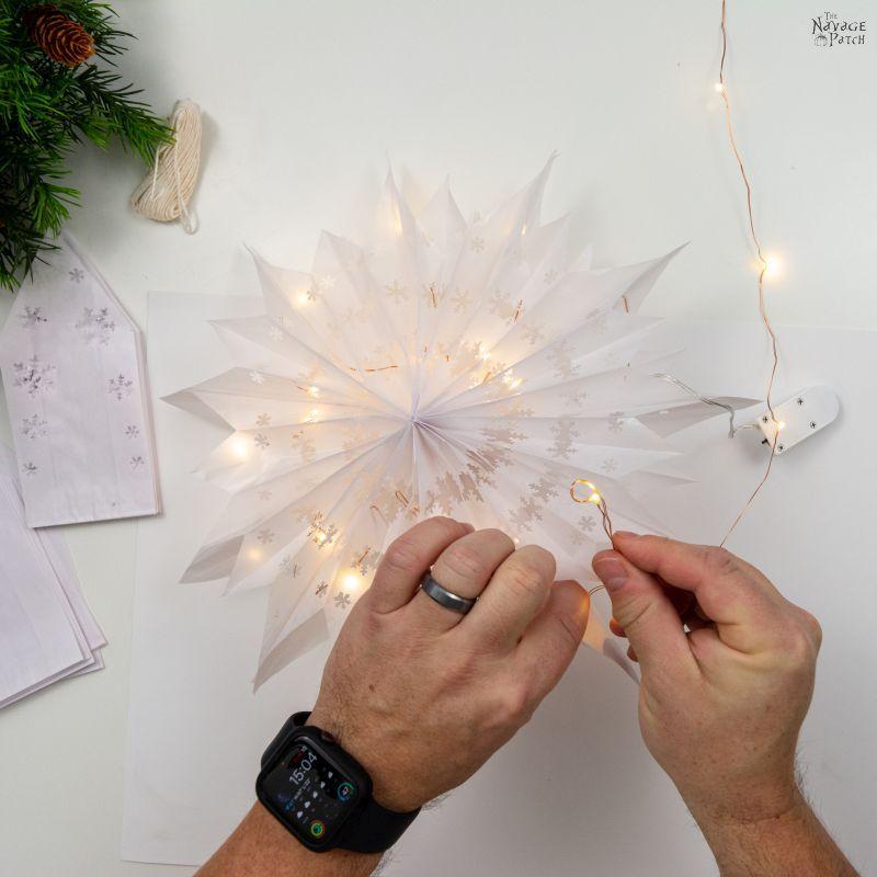 weaving fairy lights through a paper snowflake star