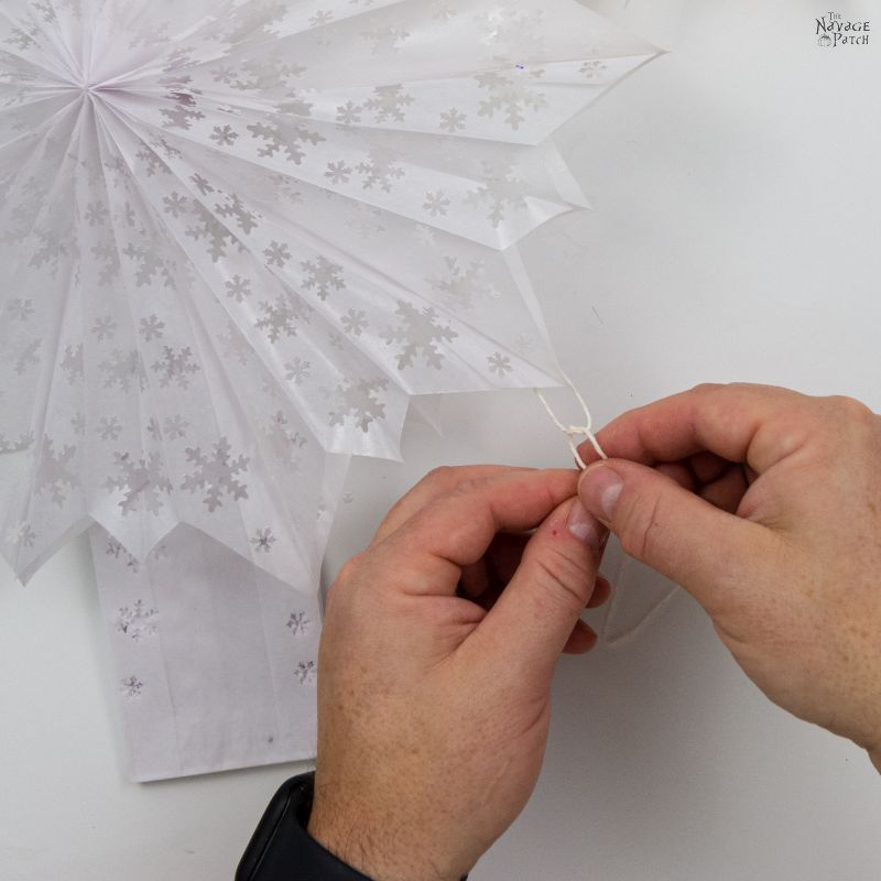 tying a string to hang a 3-d paper snowflake star