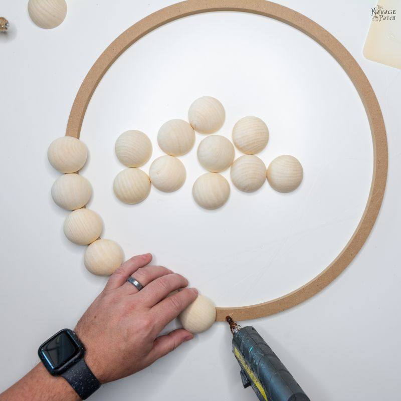 gluing wood beads toa a wreath form