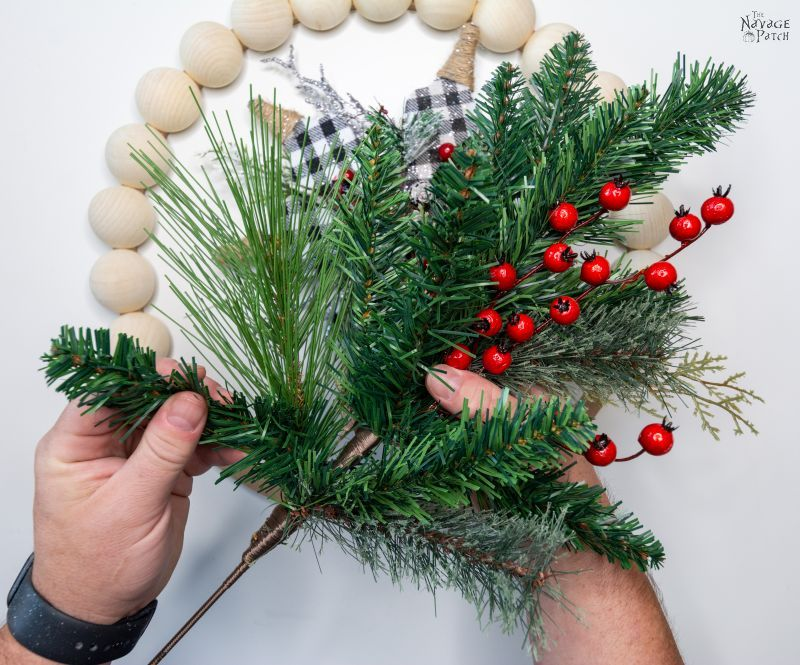 arranging floral picks for a wood bead wreath