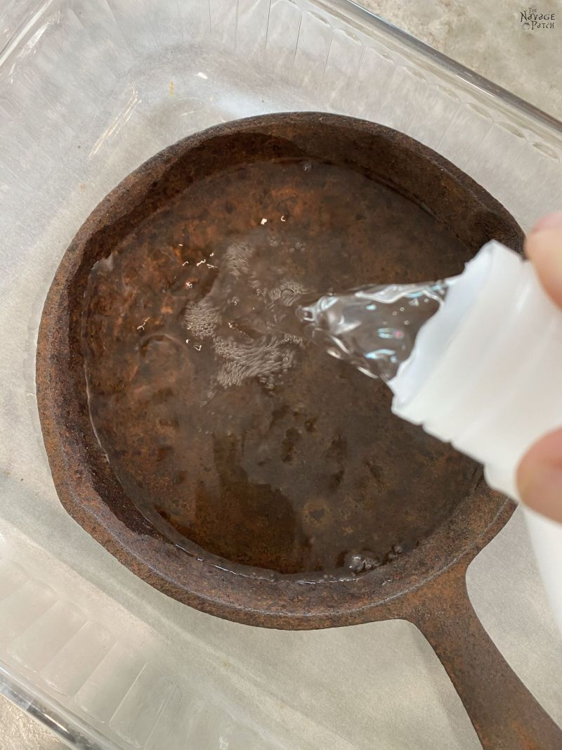 pouring vinegar on a cast iron pan
