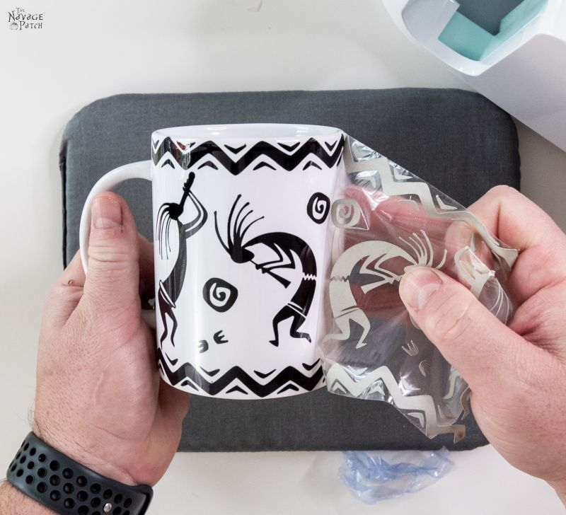 peeling a transfer sheet from a cricut mug press mug