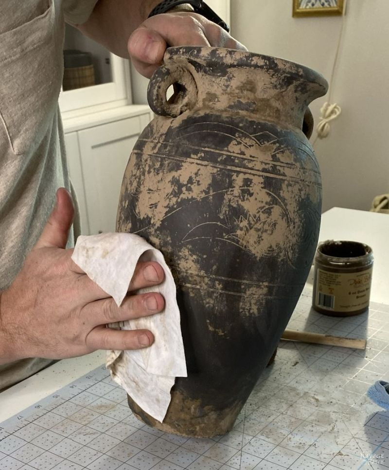 wiping mud paint from a vase