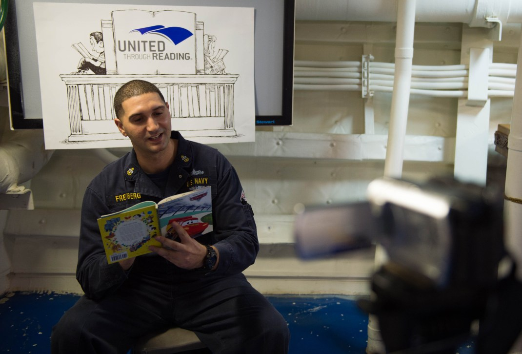 160301-N-GR718-002 PACIFIC OCEAN (March 1, 2016) Chief Culinary Specialist Kristopher Freyberg reads a book on video as part of the United Through Reading program aboard amphibious transport dock ship USS New Orleans. United through reading connects Sailors and Marines to their loved ones through video recorded sessions. More than 4,500 Sailors and Marines from the Boxer Amphibious Ready Group, 13th Marine Expeditionary Unit (13th MEU) team are currently transiting the Pacific Ocean in the 7th Fleet area of operations during a scheduled deployment. (U.S. Navy photo by Mass Communication Specialist 3rd Class Chelsea D. Daily/ Released)
