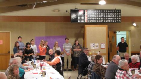Members of the NBHS Junior Class stand at the rear of the room, waiting to serve dinner at the American Legion