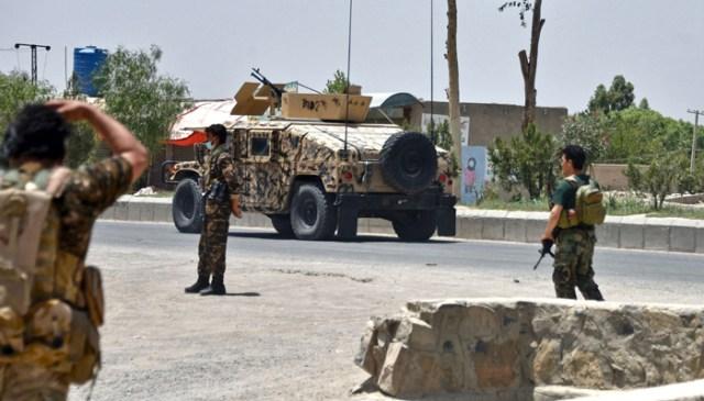 9 جولائی 2021 کو قندھار میں افغان سکیورٹی فورسز اور طالبان جنگجوؤں کے مابین جاری لڑائی کے درمیان افغان سیکیورٹی اہلکار سڑک کے کنارے محافظ کھڑے ہیں۔ - اے ایف پی
