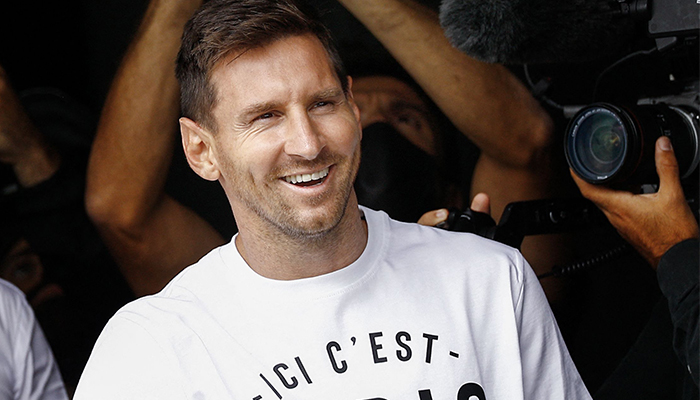 Argentinian football player Lionel Messi salutes supporters from a window after he landed on August 10, 2021 at Le Bourget airport, north of Paris. — AFP