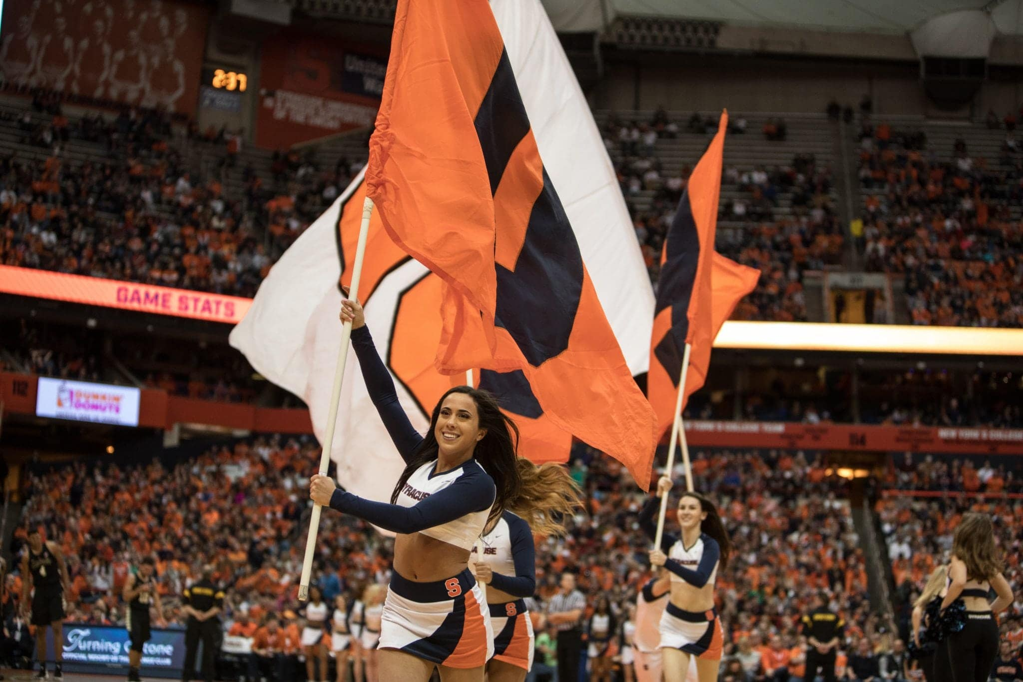 Syracuse cheerleaders carry the flags during the Wake Forest game