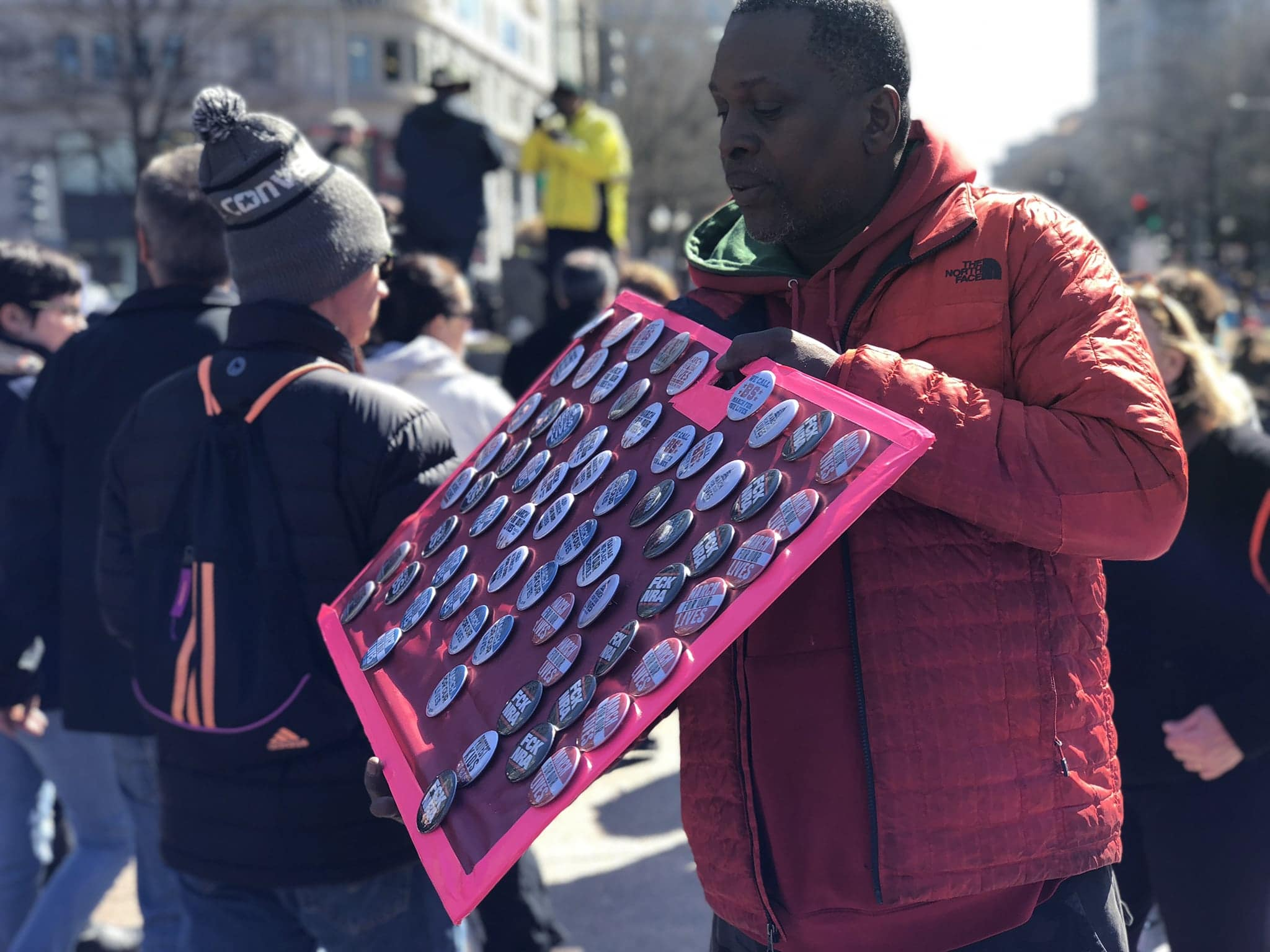 A vendor sells buttons at march