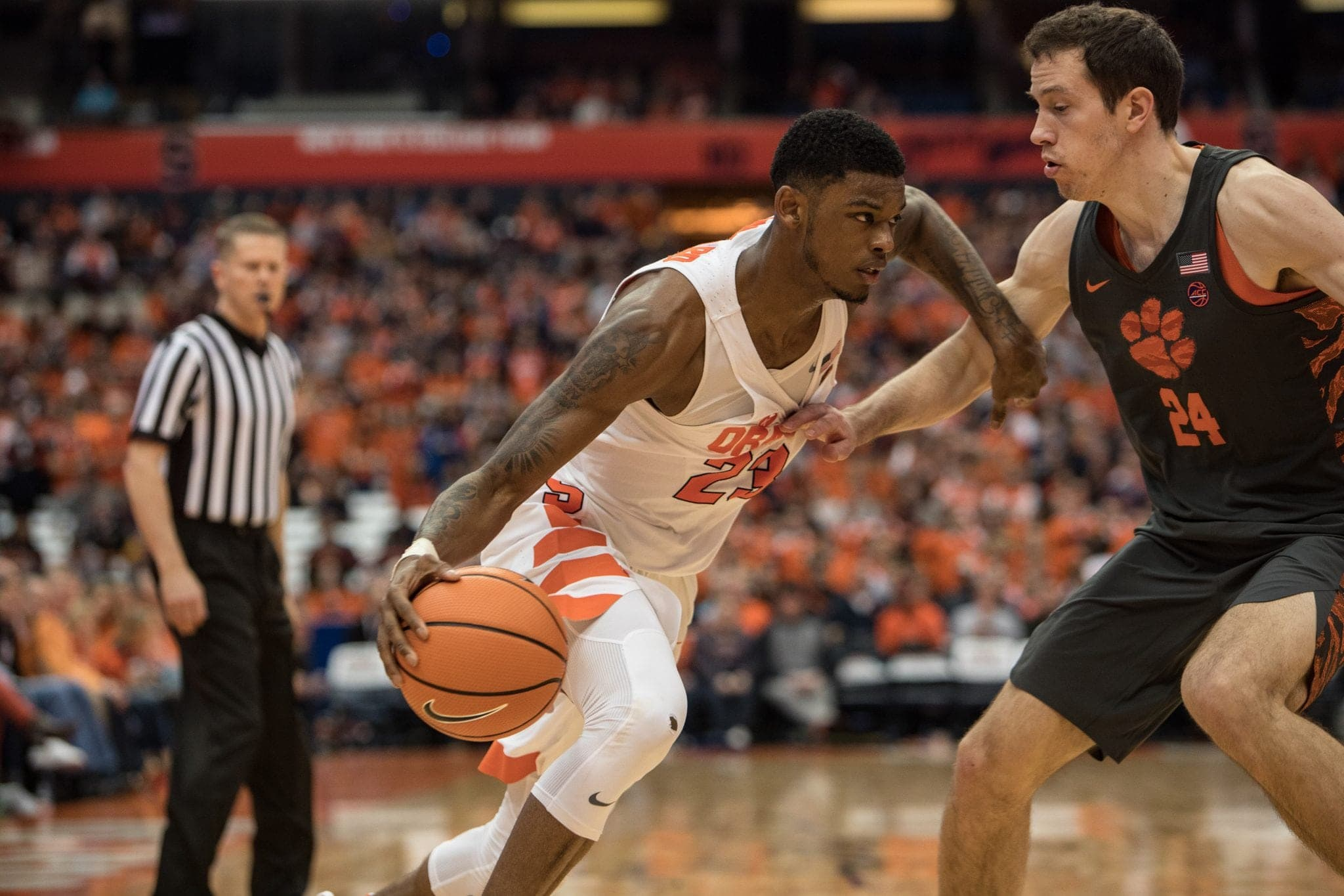 Frank Howard holds off a Clemson player as he drives for the basket.