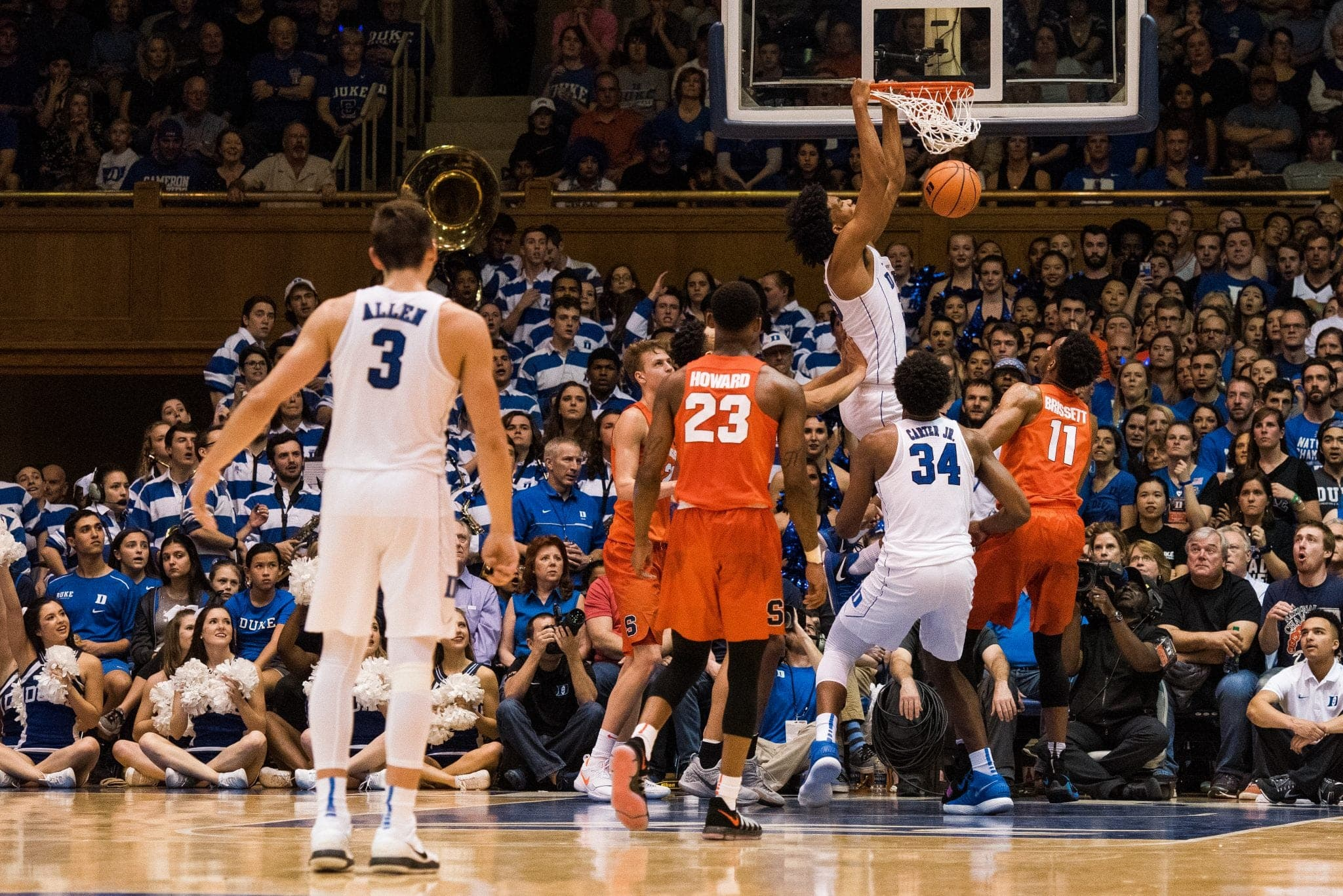 Duke player hangs on the rim during game against SU.