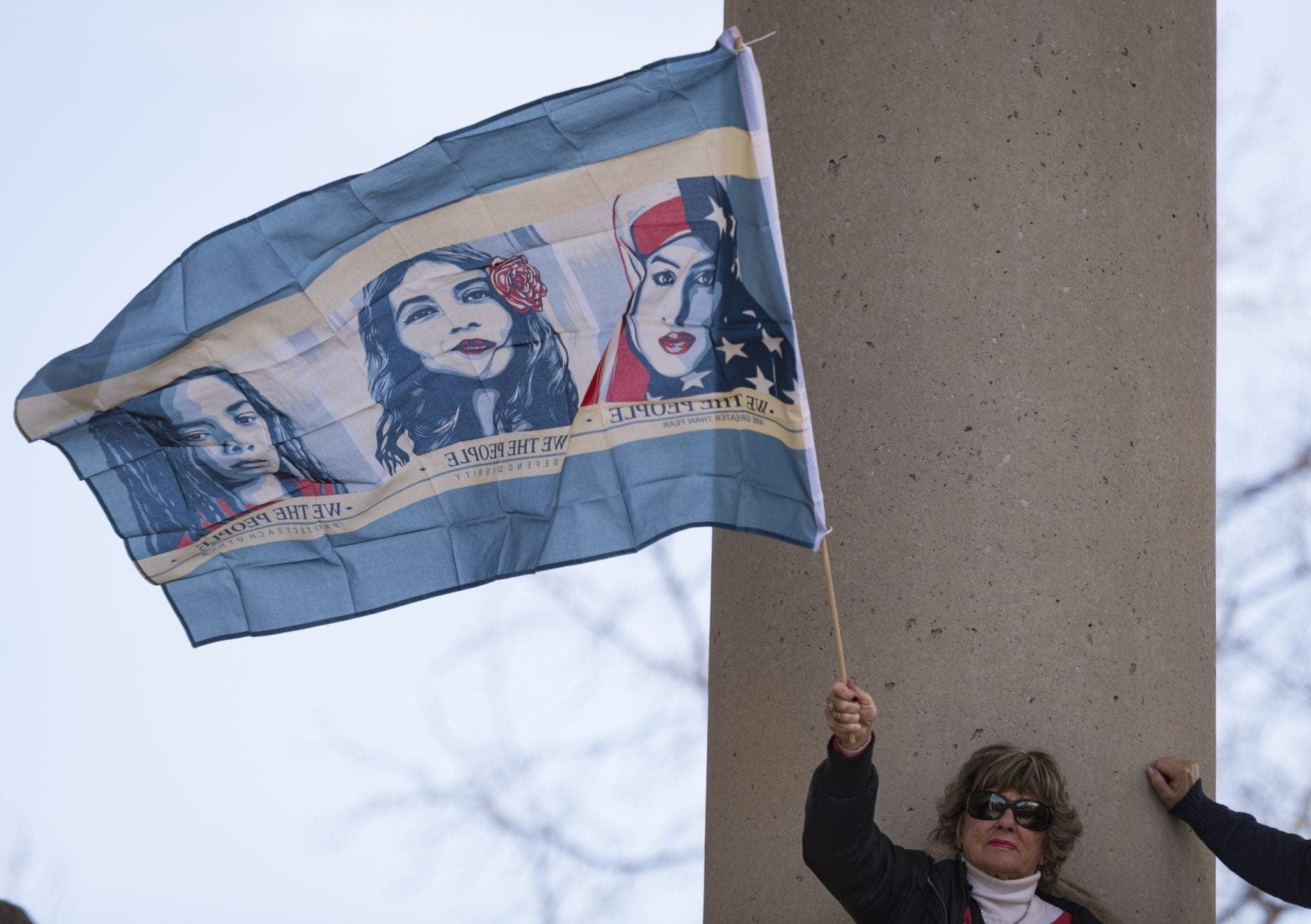 "A marcher holds a ""We The People"" flag"
