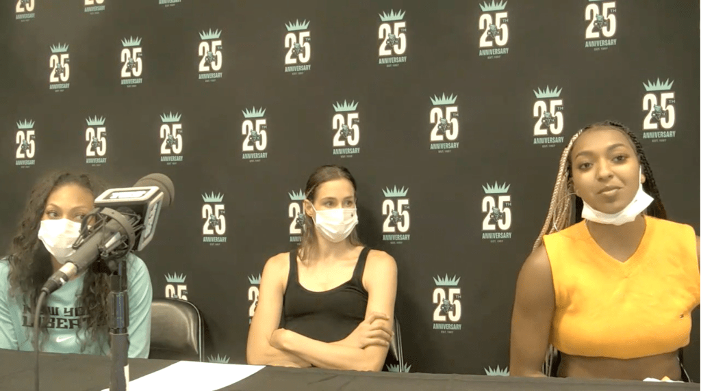 DiDi Richards of the New York Liberty talks to media postgame while Betnijah Laney and Rebecca Allen look on, August 25, 2021. (Screenshot via WNBA Content Network)