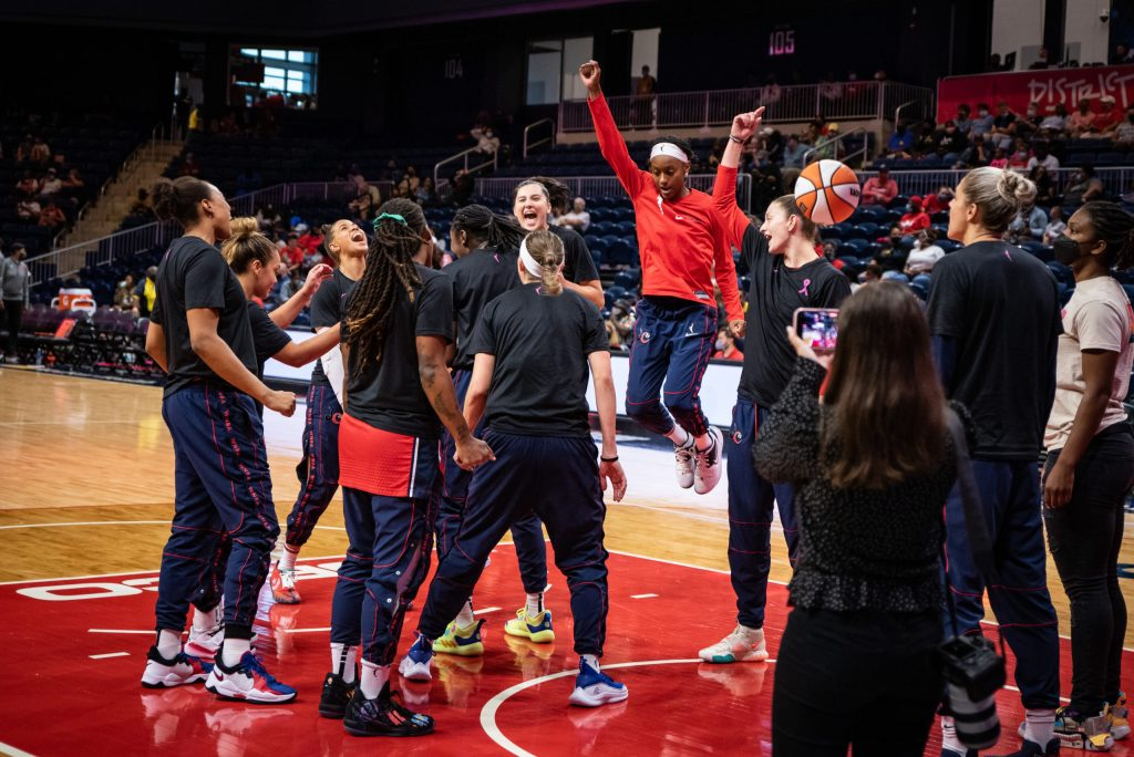 The Washington Mystics, including guard Shatori Walker-Kimbrough (center, in red), get hyped before a game against the Atlanta Dream on Sept. 10, 2021. (Photo credit: Domenic Allegra)