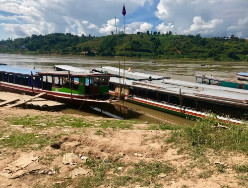 slow boats docked on mekong river