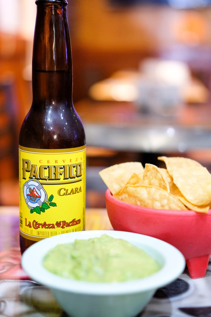 Close up of guac and chips and Pacifico beer.