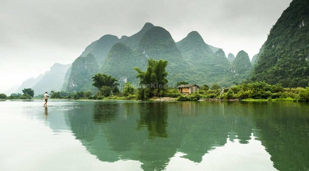 A barefoot man walks across the Li River near Yangshuo, China.