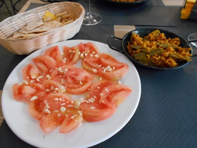 Vegan paella de verduras and tomato salad
