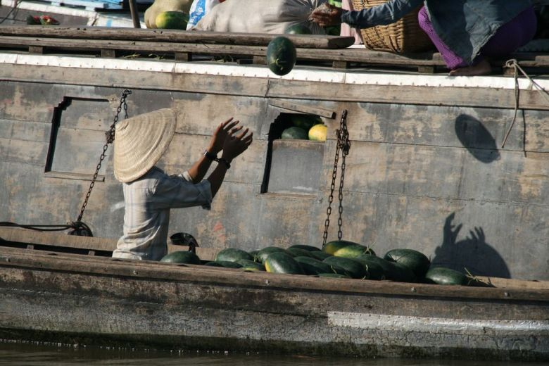 Catching watermelons at a floating market in the Mekong Delta, Vietnam