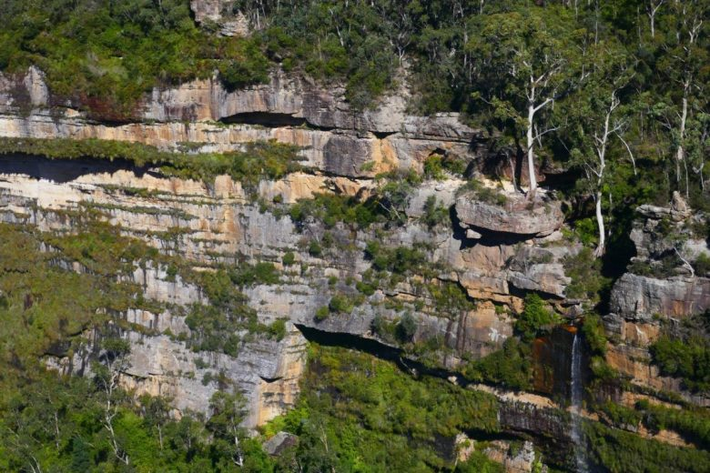 A view of cliffs and a waterfall from one of the lookouts on the trail from Govett's Leap to Pulpit Rock, near Blackheath in the Blue Mountains
