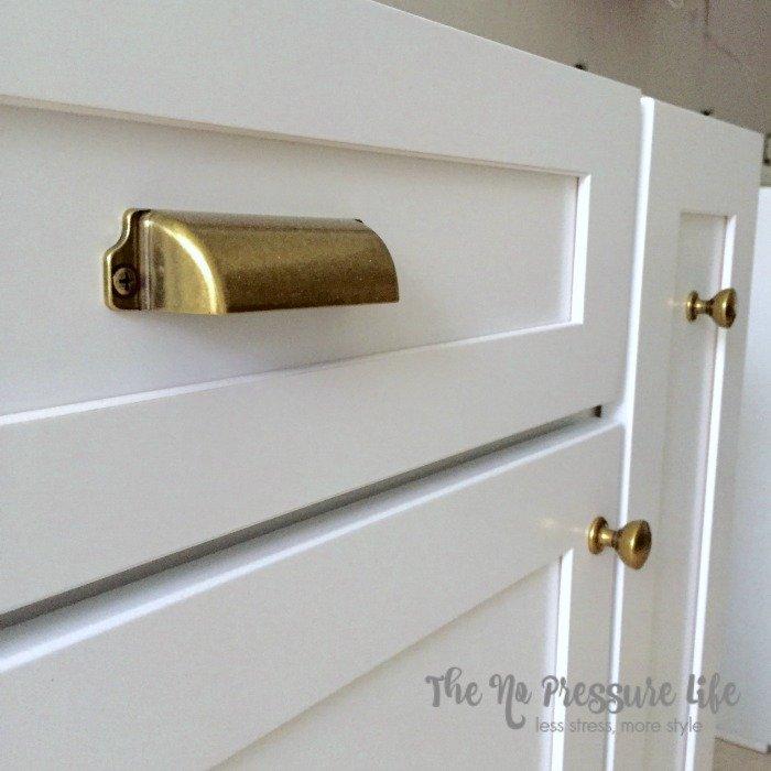 Martha Stewart Living brass hardware on white kitchen cabinets