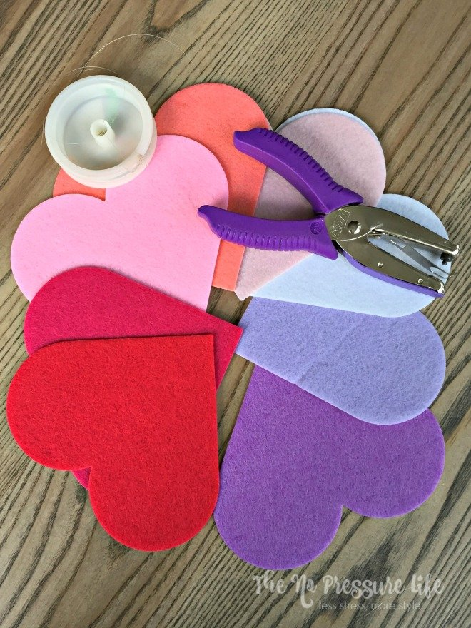 DIY Valentine's Day Mantel Decorations - Felt hearts and a hole punch on a wood table