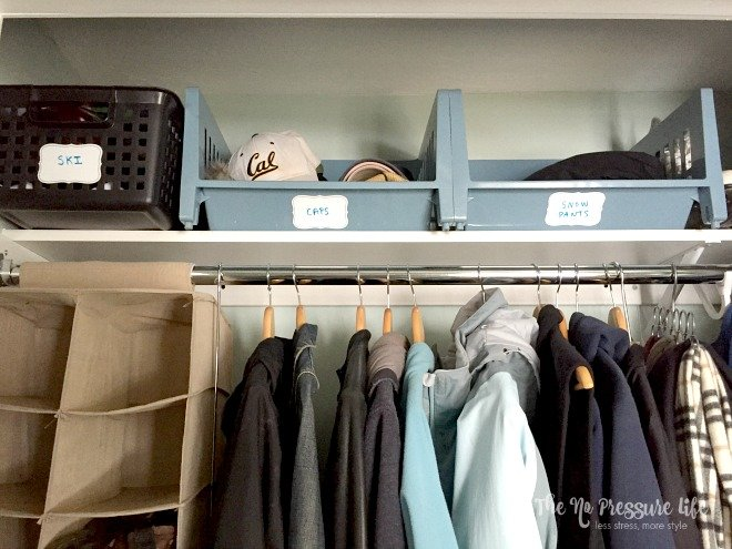 Organizing winter gear - how to organize winter gear in a coat closet with baskets on a shelf for ski gear, baseball caps, and snow pants.