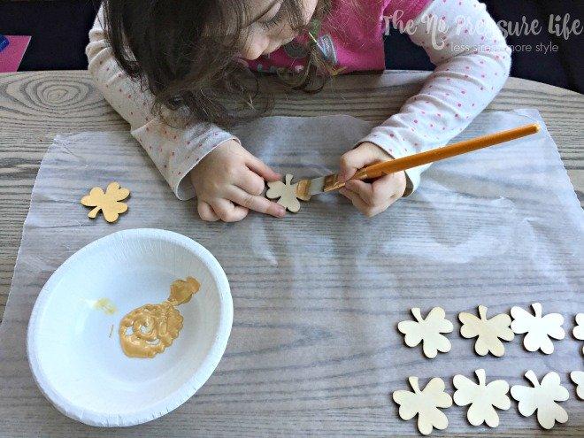 painting wood shamrocks gold for a shamrock craft