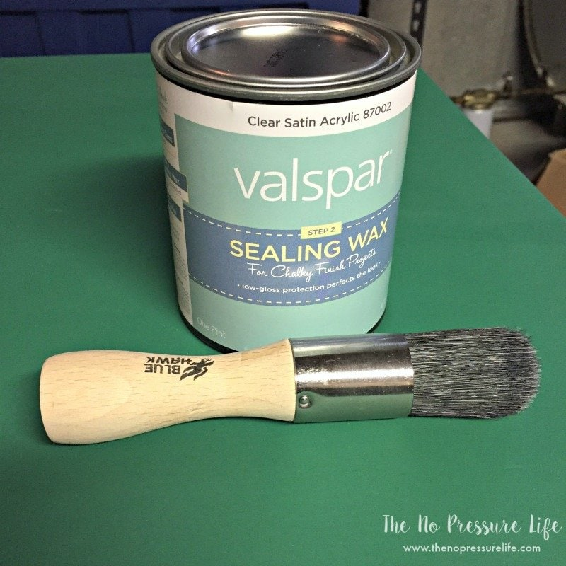 Closed can of chalk paint sealing wax and a paint brush for wax on top of a green painted desk.