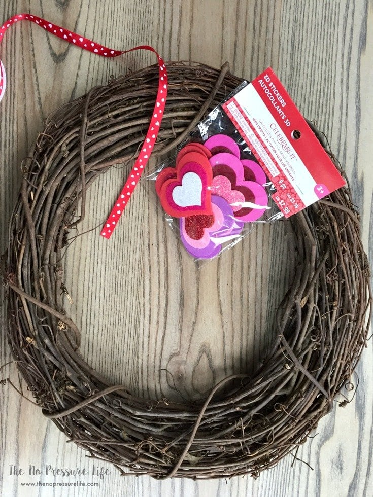 DIY Valentine's Day wreath supplies - grapevine wreath form, heart stickers, and red ribbon